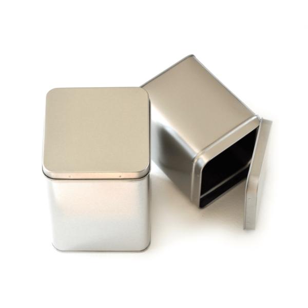 two seed storage metal tins